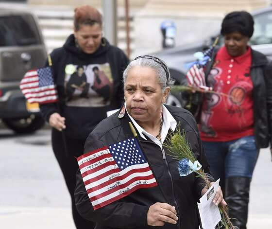 Families carry flags with the name of crime victims written on them as they approach the Crime Victims Ceremony of Remembrance at Albany's Academy Park on Thursday. The ceremony was part of the region's recognition during Crime Victims Week. (Skip Dickstein / Times Union)