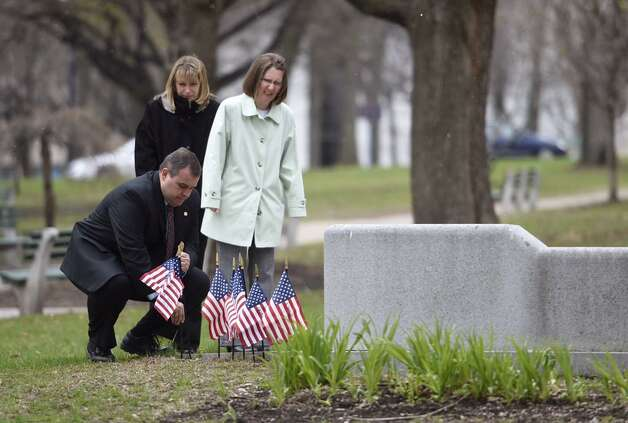 Bethlehem police Detective Sgt. Adam Hornick places a flag at the Crime Victims Ceremony of Remembrance at Albany's Academy Park on Thursday. The ceremony was part of the region's recognition during Crime Victims Week. (Skip Dickstein / Times Union)