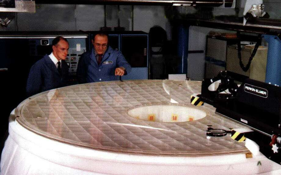 Lou Montagnino, right, points out details of the Hubble Space Telescope primary mirror to Terry Facey, left, at the Perkin-Elmer facility in Danbury in the early 1980s. Montagnino was one of the Perkin-Elmer staff responsible for completing the 94.5 inch mirror. That mirror's tiny flaw once thought catastrophic has been corrected and  Hubble is now considered one of the greatest scientic instruments in history. Photo: Contributed Photo, ST / The News-Times Contributed