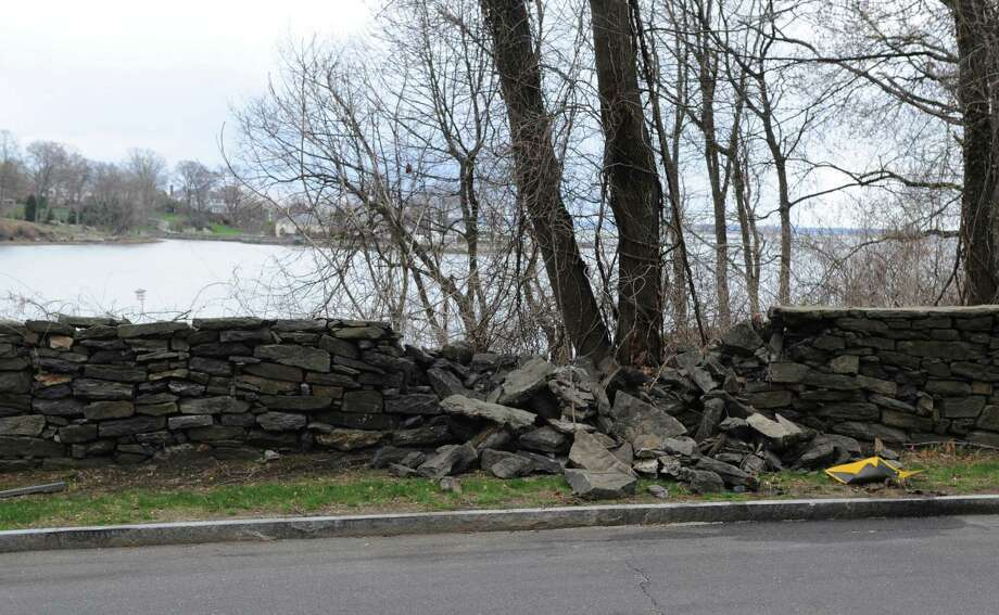 A portion of the wall blocking a view of the Long Island Sound is crumbled to the ground along Ritch Avenue West in the Byram section of Greenwich, Conn. Thursday, April 23, 2015.  The wall, which has had stability problems in the past, blocks a view of the Long Island Sound and the question has been raised whether the town should knock it down. Photo: Tyler Sizemore / Greenwich Time