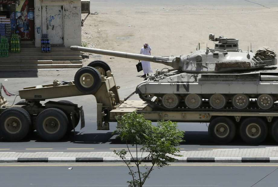 A man looks at a tank being transported in the city of Najran, Saudi Arabia, near the Yemen border. Photo: Hasan Jamali, Associated Press