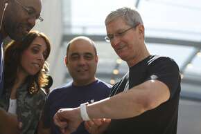 *** BESTPIX *** PALO ALTO, CA - APRIL 10: Apple CEO Tim Cook displays his personal Apple Watch to customers at an Apple Store on April 10, 2015 in Palo Alto, California. The pre-orders of the highly-anticipated wearable from the tech giant begins today as the watches arrive at stores for customers to preview.
