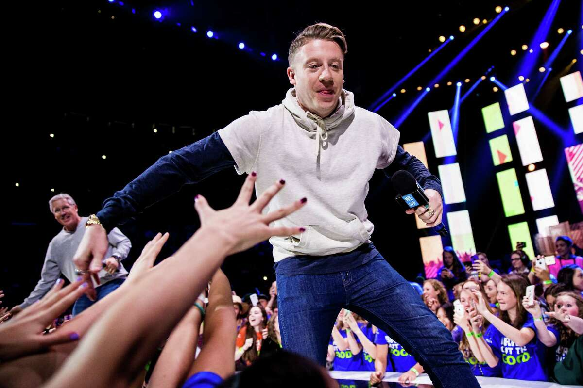 Seattle hip hop artist Macklemore greets fans before introducing Seahawks head coach Pete Carroll, left, during the annual