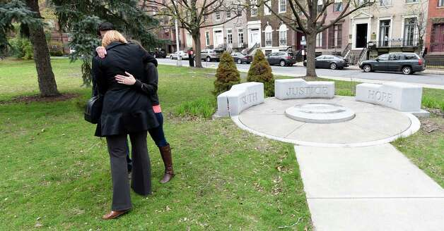 A crime victims family embraces at the Albany County Crime Victims Memorial in Thursday afternoon April 23, 2015 after the service for crime victims was held in the Albany County Courthouse in Albany, N.Y.           (Skip Dickstein/Times Union) Photo: SKIP DICKSTEIN / 00031560A