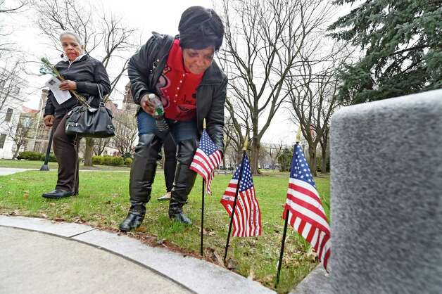 A crime victims family member, Carol Richardson who's son, El-I-Meek Rouse, who was murdered, places a flag with his name inscribed on it at the Albany County Crime Victims Memorial in Thursday afternoon April 23, 2015 after the service for crime victims was held in the Albany County Courthouse in Albany, N.Y.           (Skip Dickstein/Times Union) Photo: SKIP DICKSTEIN / 00031560A
