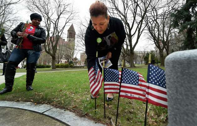 A crime victims family member, Danielle Williams places a flag at the Albany County Crime Victims Memorial in Thursday afternoon April 23, 2015 after the service for crime victims was held in the Albany County Courthouse in Albany, N.Y.           (Skip Dickstein/Times Union) Photo: SKIP DICKSTEIN / 00031560A