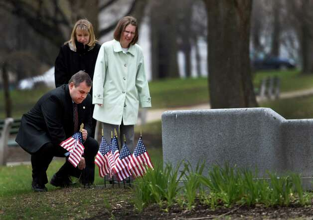 Detective Sargent Adam Hornick of the Bethlehem Police Department is joined by a crime victims familyas he places a flag at the Albany County Crime Victims Memorial in Thursday afternoon April 23, 2015 after the service for crime victims was held in the Albany County Courthouse in Albany, N.Y.           (Skip Dickstein/Times Union) Photo: SKIP DICKSTEIN / 00031560A
