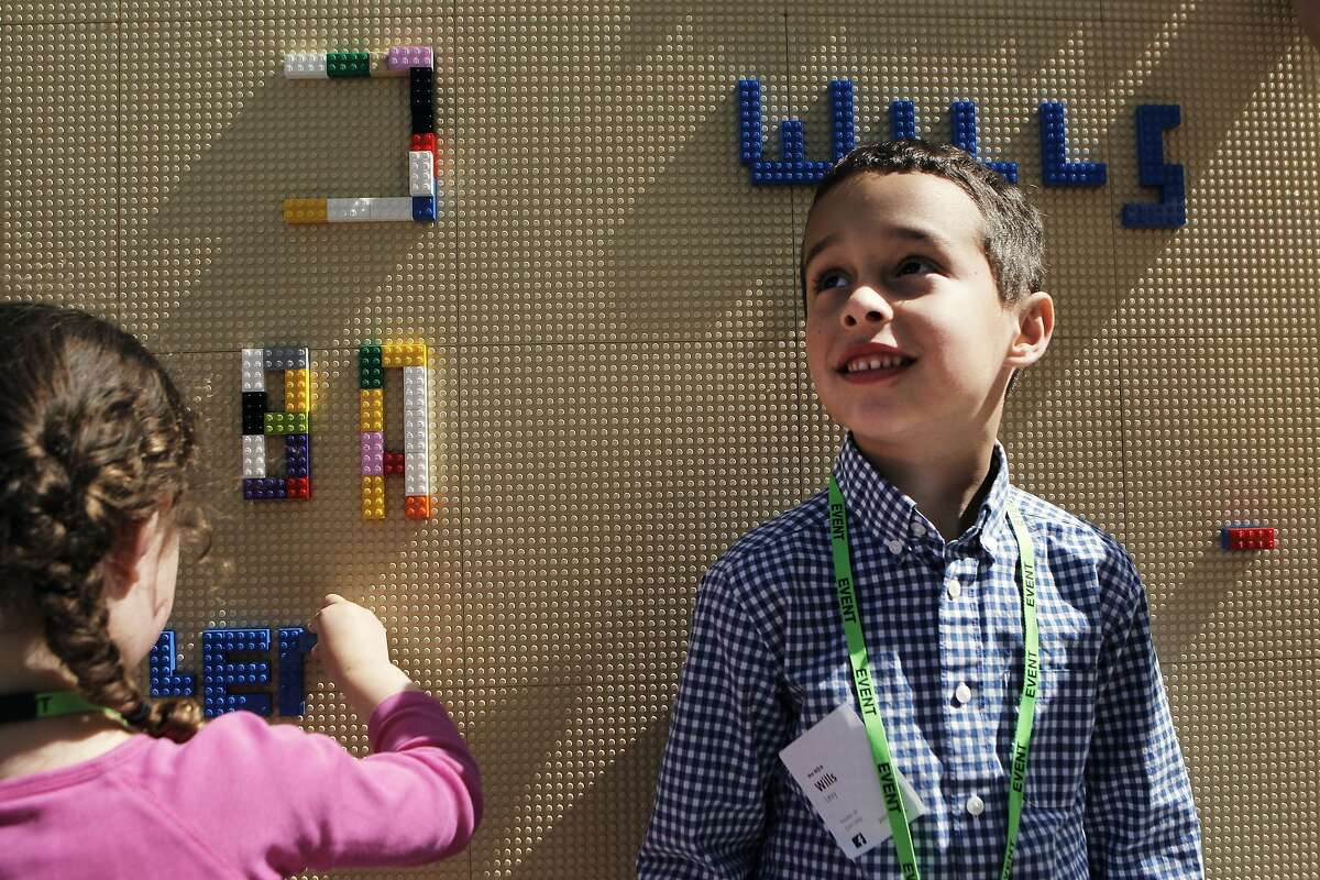 Facebook executive Dan Levy look his kids, Lea (3 and a half) and Wills (5 and a half) to Take Your Child to Work Day in Hacker Square on Facebook's campus in Menlo Park, Calif., Saturday April 23, 2015.