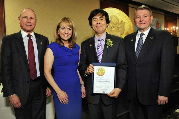 Jefferson Award finalist Wook-Jin Hwang, second from right, joins James Reed, president and CEO of St. Peter's Health Partners, left; Benita Zahn of NewsChannel 13, second from left; and Stephen Baboulis, vice president and general manager of WNYT/WNYA, at the awards dinner on Thursday, April 23, 2015, at the Century House in Latham, N.Y. (Cindy Schultz / Times Union) Photo: Cindy Schultz / 00031490A