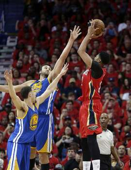 New Orleans Pelicans forward Anthony Davis (23) shoots against Golden State Warriors center Andrew Bogut and guard Klay Thompson, bottom left, during the first half of Game 3 of a first-round NBA basketball playoff series Thursday, April 23, 2015, in New Orleans. (AP Photo/Gerald Herbert)