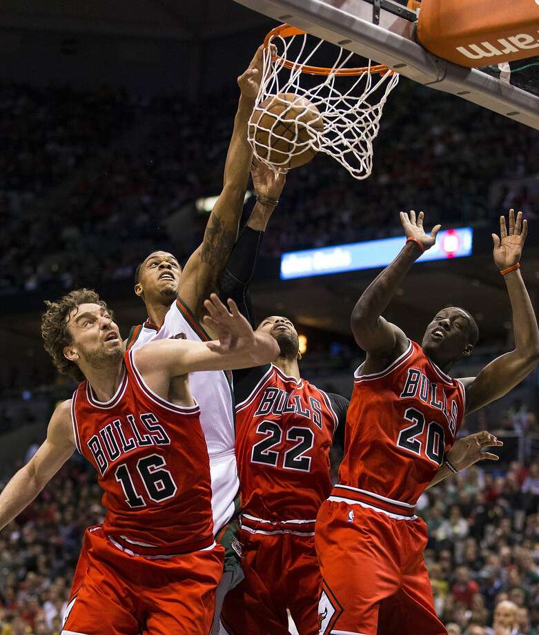 Forward Khris Middleton (background) of the Bucks scores over center Pau Gasol (16), forward Taj Gibson (22) and forward Tony Snell (20) of the Bulls in the first quarter at Bradley Center in Milwaukee on Thursday night. The Bulls won in two overtimes. Photo: Tom Lynn