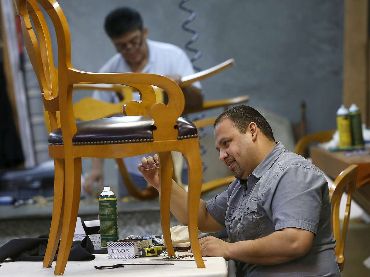 Upholsterers Darwin Medrano (right) and Angel Herrera (back) work on chairs at Franciscan Interiors in San Francisco, California, on Wednesday, April 22, 2015.