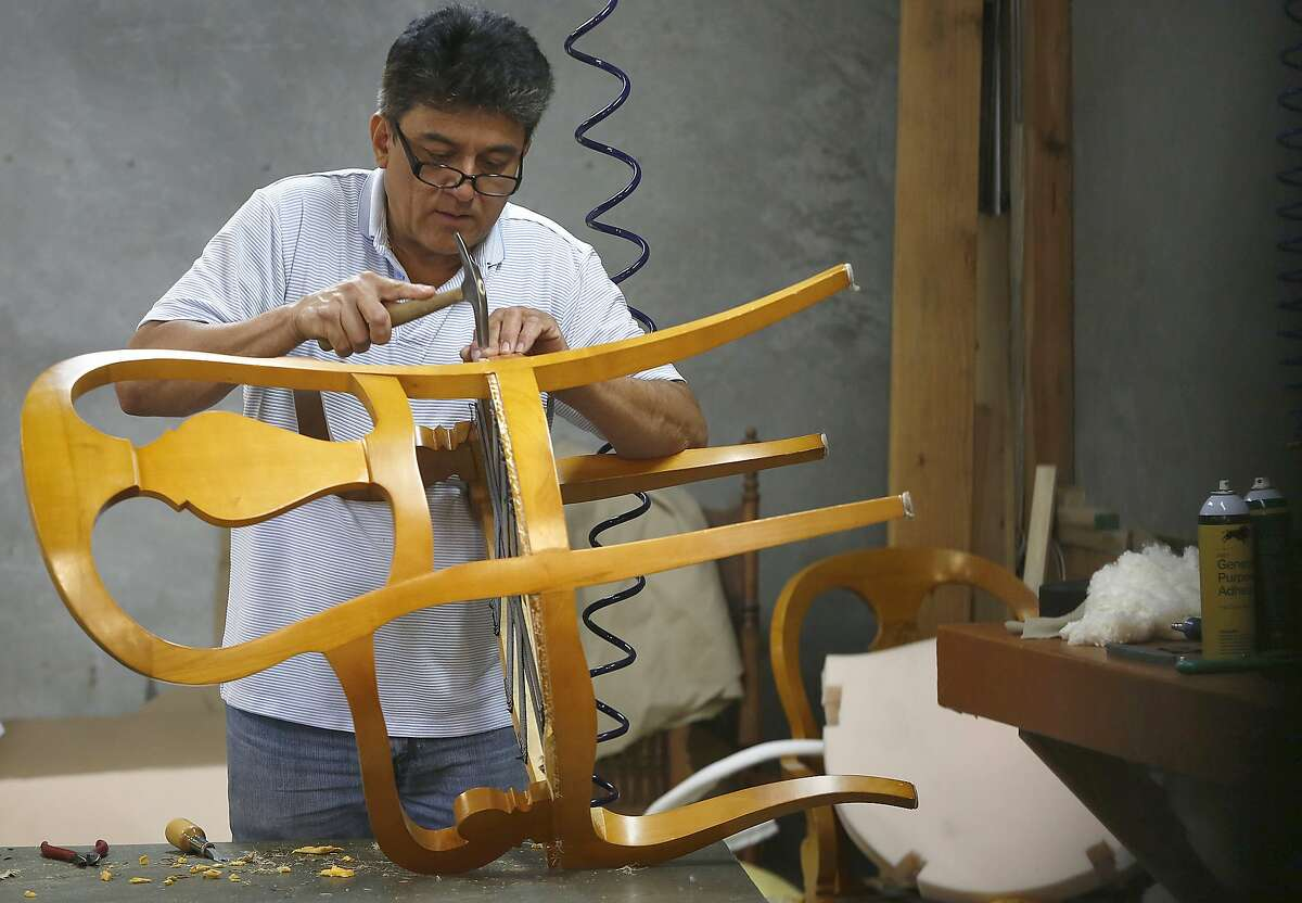 Upholsterer Angel Herrera works on a chair at Franciscan Interiors in San Francisco, California, on Wednesday, April 22, 2015.