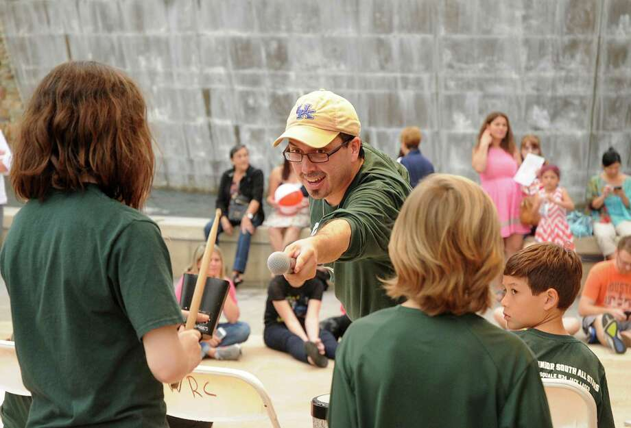 Ralph Hicks, of The Woodlands, founder of the Let Them Drum uses his microphone as drummers perform during the Live at Night concert series at all-new Waterway Square on The Woodlands Waterway. The Waterway Square now has a new permanent entertainment stage and concession stands. a concert will be held every Saturday night from April 18 to May 9th at The Waterway Square. Photograph by David Hopper Photo: David Hopper, Freelance / freelance
