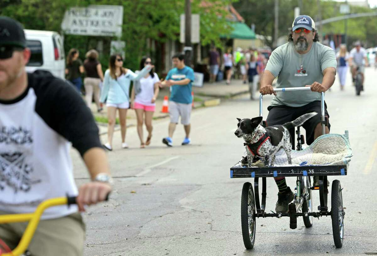 Orlando Perez of Houston gives his dog, Buddy, at ride along Westheimer during the Cigna Sunday Streets Sunday on March 29, 2015.