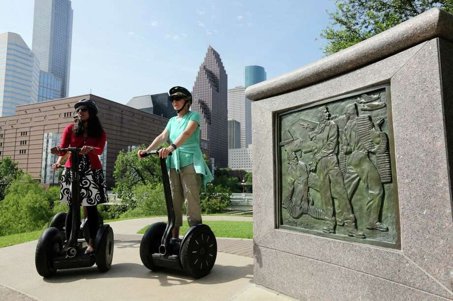 Segway riders Tania Hossain, left, and Terry Long learn about the history behind the monument dedicated to former President George H.W. Bush during a city tour. Photo: Mayra Beltran, Staff / © 2015 Houston Chronicle