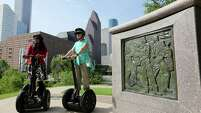 Segway riders Tania Hossain, left, and Terry Long learn about the history behind the monument dedicated to former President George H.W. Bush during a city tour.