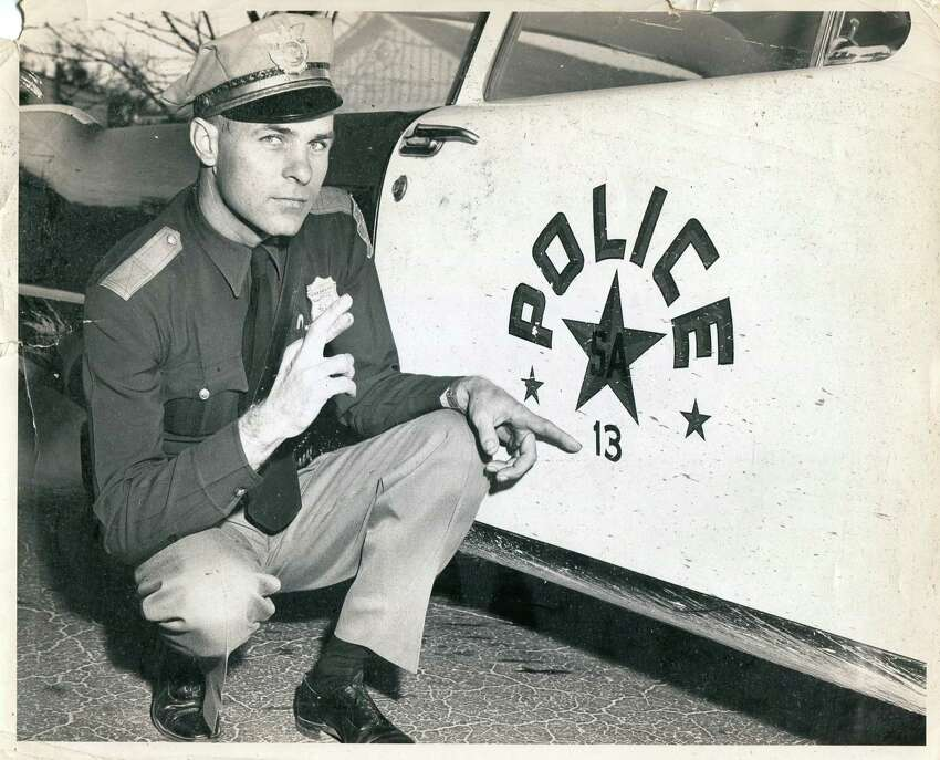 In this unmarked photo, an officer crosses his finger for luck for he's driving car #13.