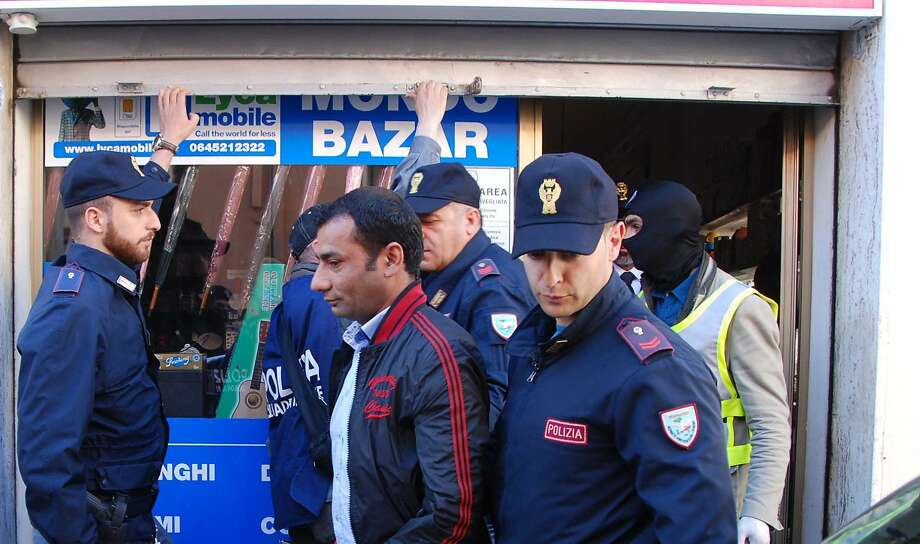Italian police officers arrest a suspect in Olbia, Italy. Islamic extremists suspected in a bomb attack in a Pakistani market that killed more than 100 people had also planned an attack against the Vatican in 2010 that was never carried out, an Italian prosecutor said. Police arrested nine suspects related to the probe Friday throughout Italy. Another nine were being sought, three of whom were believed to still be in the country. Photo: Antonio Satta, Associated Press