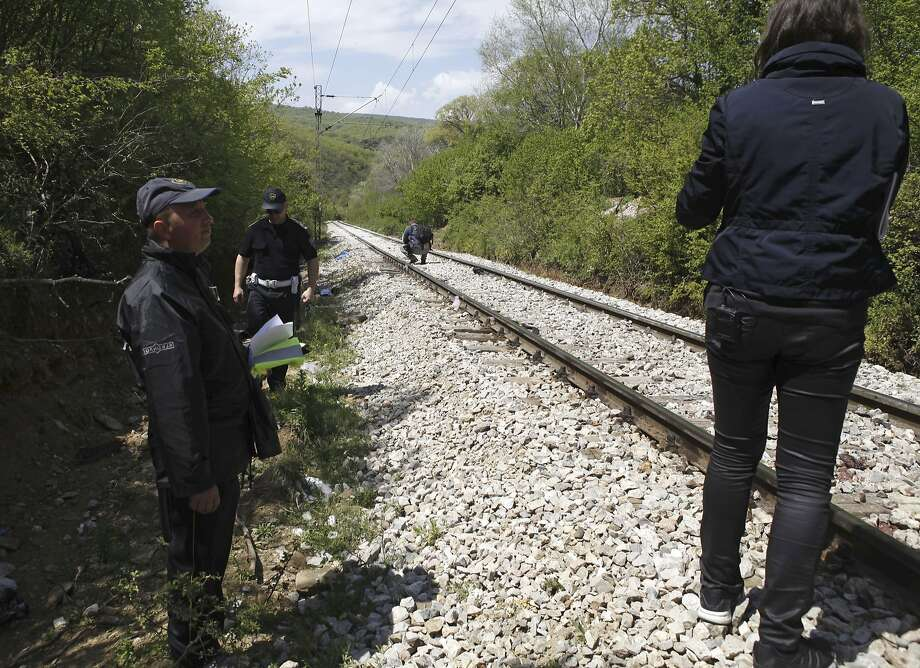 Police officers inspect the area along the train tracks where the refugees were killed Thursday. Photo: Boris Grdanoski, Associated Press