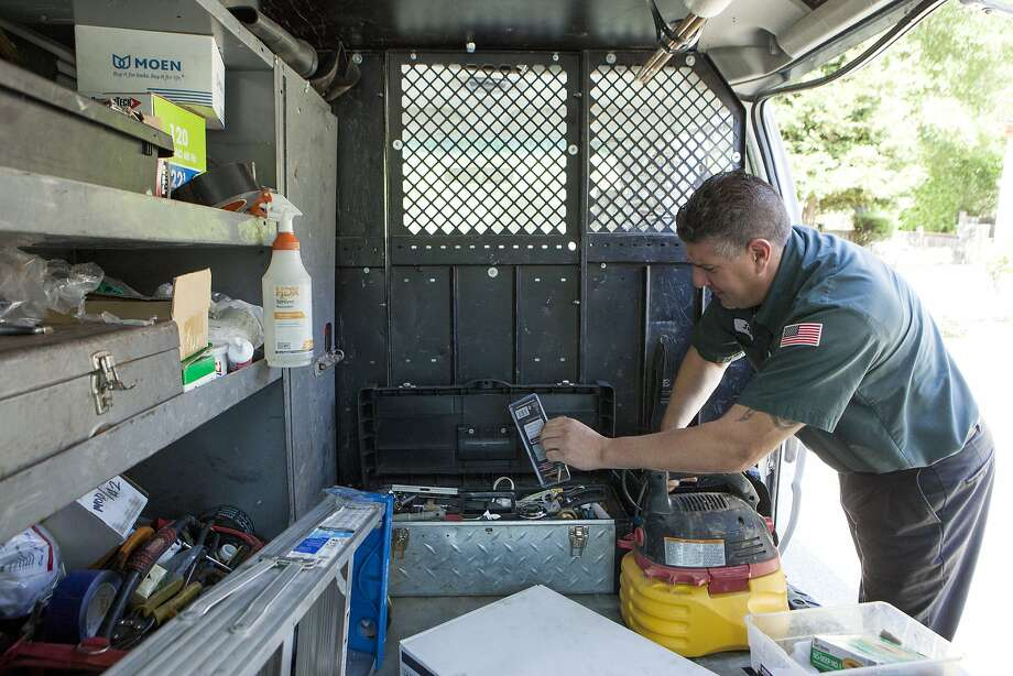 Jeff, a plumber from Stewart Heating, Air and Plumbing, grabs tools from his toolbox outside a clients home where he'll install a new toilet, Friday, April 24, 2015, in San Ramon, Calif. The company signed up with Angie's List and Amazon Home Services to generate more work and leads when business was slow. Under the Angie's List system, workers can retain customers and go back to work for them directly in the future, often making more money. Photo: Santiago Mejia, The Chronicle