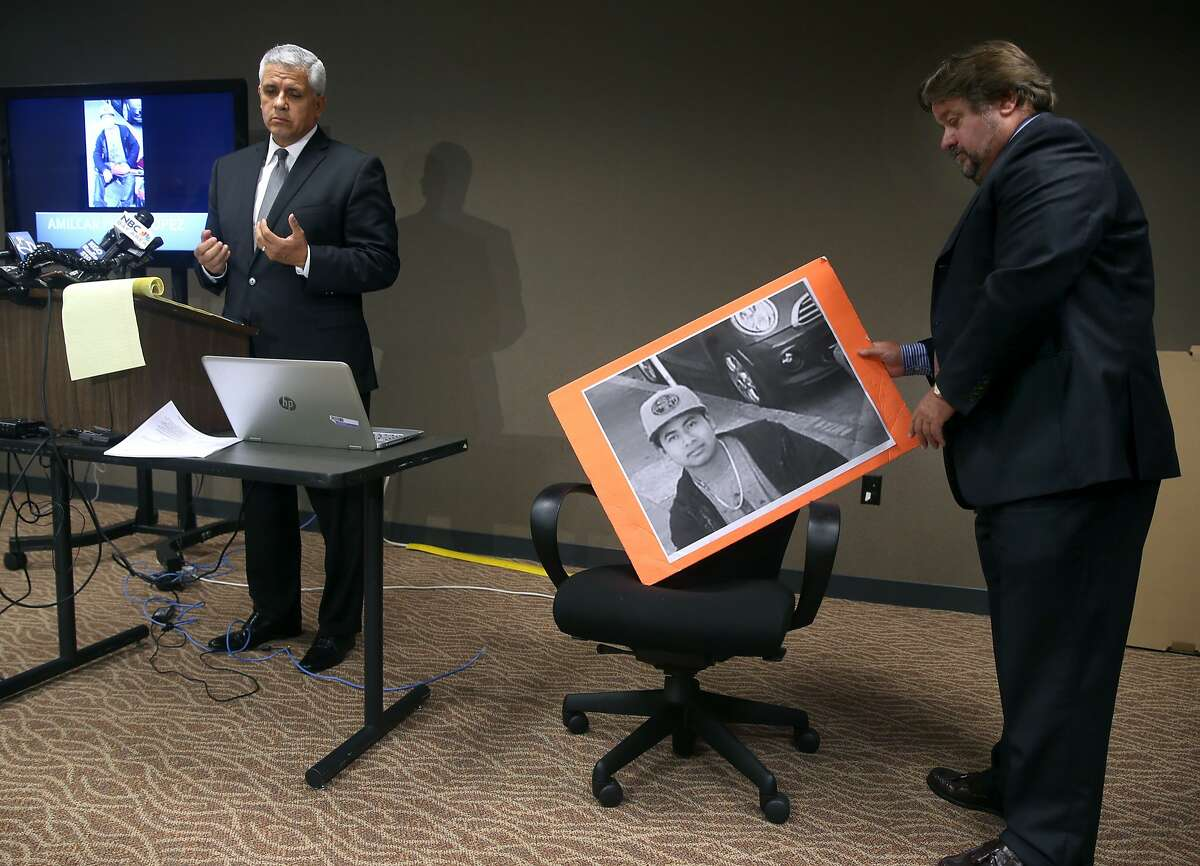 Agustin Pradillo adjusts a large photograph of Amilcar Perez Lopez as attorney Arnoldo Casillas (left) announces a federal lawsuit has been filed against the police department and Chief Greg Suhr, at a new conference in San Francisco, Calif. on Friday, April 24, 2015. Attorneys allege that police officers killed Lopez on Feb. 26 while he was running from police, disputing the department's version that Lopez had lunged at officers with a knife.