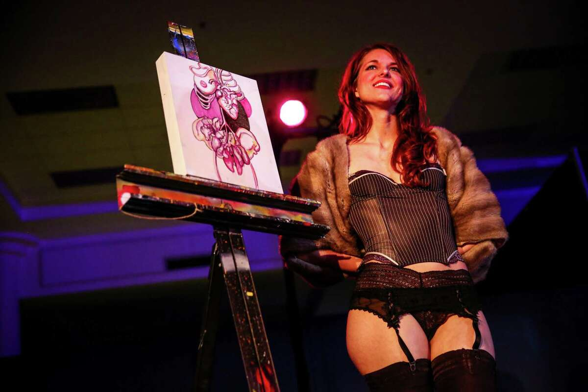 Artist Michelle Anderst stands next to a painting she created live during the Erotic Art Festival's artist