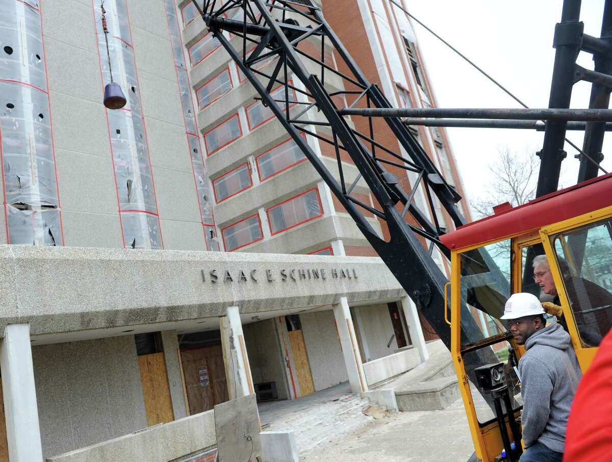 Jerry Olivier, a mechanical engineering graduate student, sits in a crane cab as the wrecking ball strikes Schine Hall as demolition of the 10-story University of Bridgeport residence hall begins Friday, April 24, 2015. Olivier won a raffle to take the ceremonious first swing.
