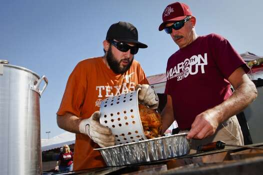 Longhorns fan Ben Hovland, left, and his Aggies fan dad Bruce Hovland, right, fry a turkey during their Thanksgiving Day tailgate before the start of the Texas A&M Aggies vs University of Texas Longhorns rivalry NCAA football game at Kyle Field on Thursday, November 24, 2011 in College Station, Texas. (Patrick T. Fallon/The Dallas Morning News) Photo: Staff Photographer