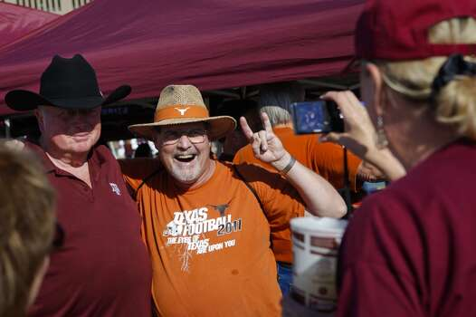 Aggies fan Barbara Hill, right, takes a photo of her husband Larry Hill, left, with Longhorns fan Scott Wilson, who has attended 420 consecutive Longhorns football games since October 1977, as they tailgate before the start of the Thanksgiving Day Texas A&M Aggies vs University of Texas Longhorns rivalry NCAA football game at Kyle Field on Thursday, November 24, 2011 in College Station, Texas. (Patrick T. Fallon/The Dallas Morning News) Photo: Staff Photographer