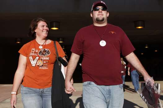 """Longhorns fan Brandi Lain, left, walks with her boyfriend Craig Moncus, right, before the start of the Texas A&M Aggies vs University of Texas Longhorns rivalry NCAA football game at Kyle Field on Thanksgiving Day, Thursday, November 24, 2011 in College Station, Texas. """"It's a pretty good family rivalry,"""" said Moncus. """"The outside of our house is painted burnt orange and the doors are painted maroon and white."""" (Patrick T. Fallon/The Dallas Morning News) Photo: Staff Photographer"""