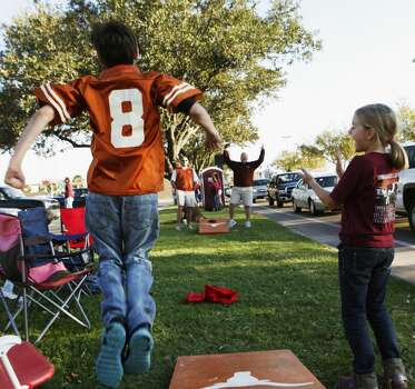 Longhorns fans Hunter Haskins, 11, front left, and his dad Butch Haskins, left, play corn hole against Aggie in-laws Tim Muench and his daughter Laney Muench, 8, right, as they tailgate before the start of the Texas A&M Aggies vs University of Texas Longhorns rivalry NCAA football game at Kyle Field on Thanksgiving Day, Thursday, November 24, 2011 in College Station, Texas. Their twin wives went to A&M and UT, respectively.  (Patrick T. Fallon/The Dallas Morning News) Photo: Staff Photographer