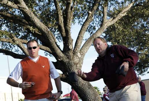 Longhorns fans Butch Haskins, left, plays corn hole against Aggie brother-in-law Tim Muench, right, as they tailgate before the start of the Texas A&M Aggies vs University of Texas Longhorns rivalry NCAA football game at Kyle Field on Thanksgiving Day, Thursday, November 24, 2011 in College Station, Texas. Their twin wives went to UT and A&M, respectively.  (Patrick T. Fallon/The Dallas Morning News) Photo: Staff Photographer
