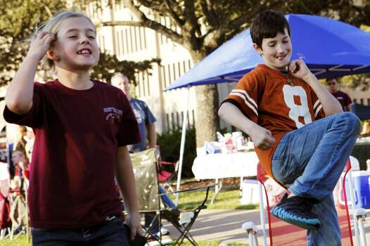 Longhorns fan Hunter Haskins, 11, right, does a victory dance while playing corn hole against his Aggie cousin Laney Muench, 8, left, as they tailgate with their family before the start of the Texas A&M Aggies vs University of Texas Longhorns rivalry NCAA football game at Kyle Field on Thanksgiving Day, Thursday, November 24, 2011 in College Station, Texas. Their twin sister mothers went to UT and A&M. (Patrick T. Fallon/The Dallas Morning News) Photo: Staff Photographer