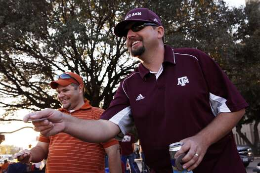 Longhorn fan Steven Gutierrez, left, and coworker Aggies fan Sam Hosch, right, play washers while tailgating before the start of the Texas A&M Aggies vs University of Texas Longhorns rivalry NCAA football game at Kyle Field on Thanksgiving Day, Thursday, November 24, 2011 in College Station, Texas. (Patrick T. Fallon/The Dallas Morning News) Photo: Staff Photographer