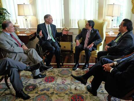 Texas Gov. Greg Abbott, second from left, and Honduras President Juan Orlando Hernandez, second from right, visit as Texas Secretary of State, Carlos Cascos, far left, and Hondoran Chancellor Arturo Corrales, far right, look on, following a meeting at the governor's mansion in Austin, Texas, on Thursday, April 23, 2015.  Abbott met with the Honduran president Thursday in his first visit with a South American leader since he took office and promised to staunch the flow of immigrants coming across the border.  (Rodolfo Gonzalez/Austin American-Statesman, Pool) Photo: Rodolfo Gonzalez, POOL / Associated Press / Pool Austin American-Statesman