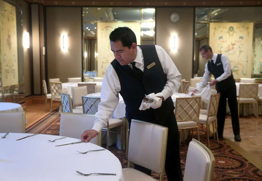 Left: Manuel Guadarrama (front) and Jim Thrail kill prepare a room for a wedding reception at the Loews Regency in S.F. Photo: Paul Chinn, The Chronicle