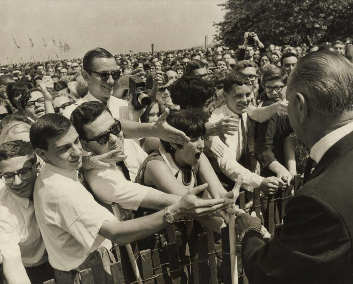 """August 18, 1966: President Lyndon Baines Johnson shakes hands with college and high school students working as interns in Washington, D.C. Charles Foster is in sunglasses, third from the left. """"I'm not the tall guy,"""" says Foster, """"but below the tall guy."""""""