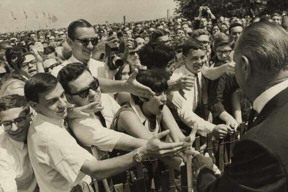 "August 18, 1966: President Lyndon Baines Johnson shakes hands with college and high school students working as interns in Washington, D.C. Charles Foster is in sunglasses, third from the left. ""I'm not the tall guy,"" says Foster, ""but below the tall guy."""