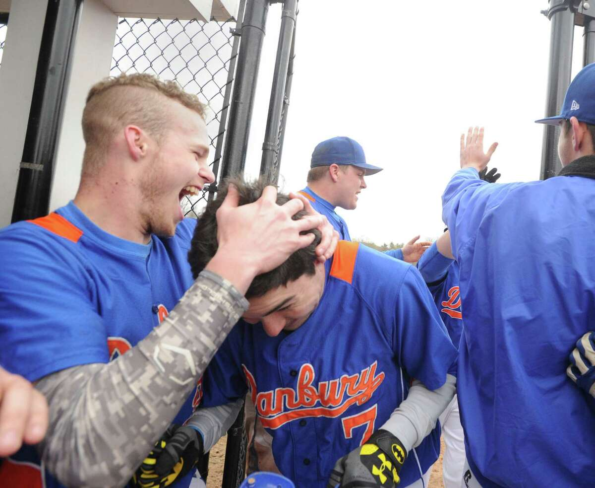 Danbury's Matt Greene, center, is congratulated by teammates including Mike Tucci, left, after Greene hit a 2 run home run in the top of the 4th inning during the high school baseball game between Westhill High School and Danbury High School at Westhill in Stamford, Conn., Friday, April 24, 2015. Danbury won the game, 11-3.