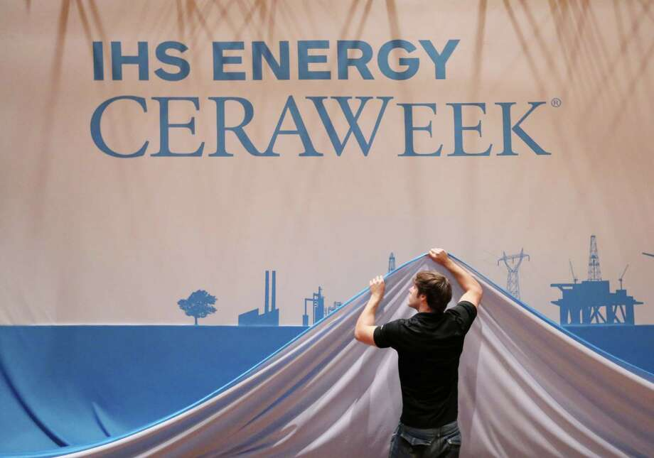 David John helps to lower a large backdrop Friday as workers take down CERAWeek trappings at the Hilton Americas Hotel in Houston. Photo: Jon Shapley /Houston Chronicle / © 2015 Houston Chronicle