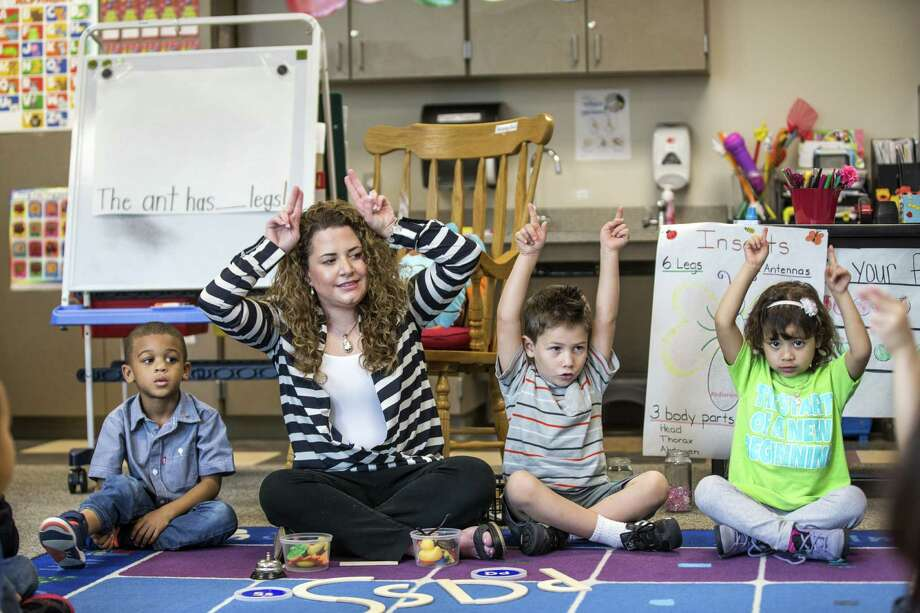 Pre-K teacher Vanessa de Simone Canseco participates in an active learning session with  her students, from left, Braylon Nicholson, Ezequiel Portillo and Hailey Barrientos, at Marshall Elementary School on Friday.  Photo: Brett Coomer, Staff / © 2015 Houston Chronicle