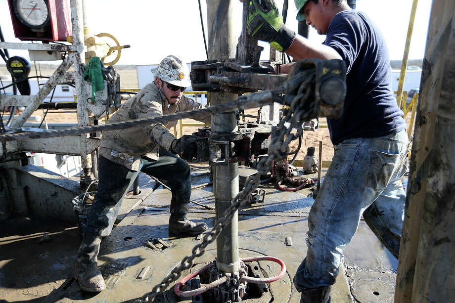 Floorhands remove pipe at a drilling site in Atascosa County. Photo: Jerry Lara /San Antonio Express-News / © 2013 San Antonio Express-News