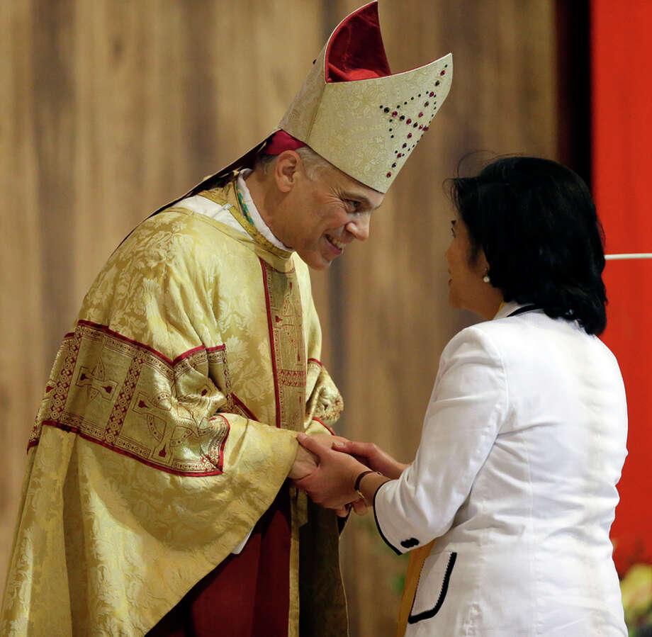 San Francisco Archbishop Salvatore Cordileone greets a parishioner at a ceremony in 2012. Photo: Marcio Jose Sanchez / Associated Press / AP POOL