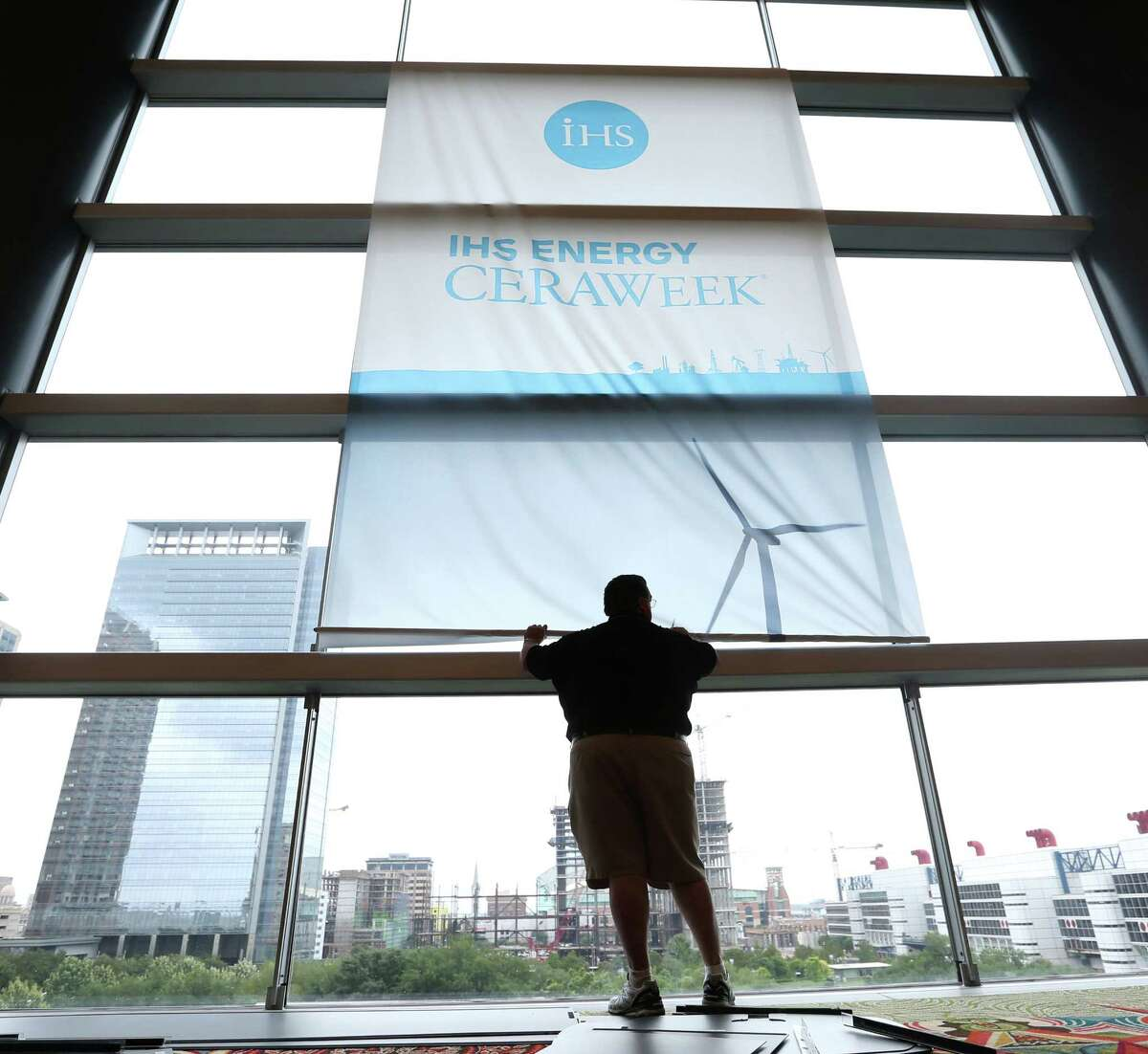 Bryce Dunahoo works Friday to lower a backdrop on the final day of the IHS Energy CERAWeek conference at the Hilton Americas-Houston downtown.