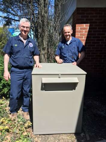 Quad Graphics agreed to let an employee build a food drop box, using company time and materials, for Franklin Community Center. The box will allow Franklin to accept donations of non-perishable items any time of day. Here, Brian Carroll, left, and Pat Rogers, the builder, deliver the box.