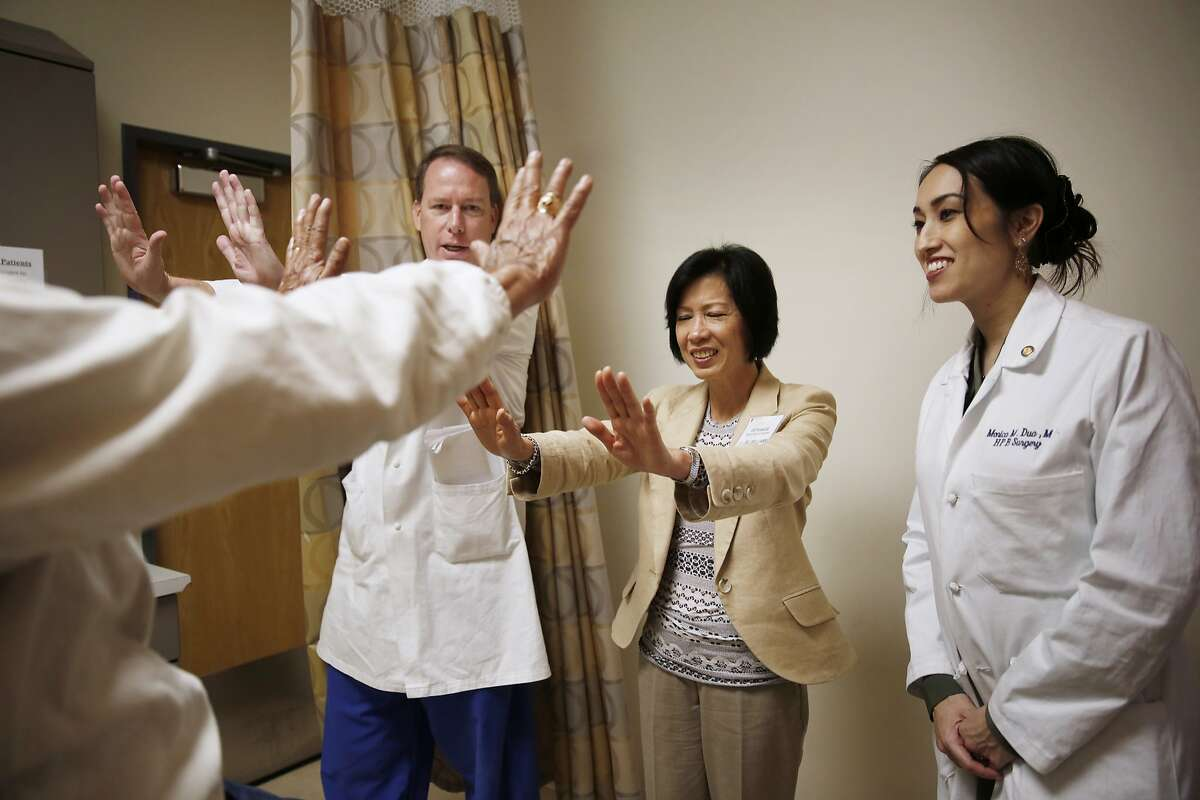 Siu Williams (second from right), certified medical interpreter, interprets instructions from Stanford transplant surgeon Andrew Bonham (second from left) for patient Son Van Vo (left) also attended by Dr. Monica Dua (right), Stanford surgeon, during an exam at a medical appointment at Stanford Medical Center on Thursday, January 29, 2014 in Stanford, Calif. Williams' certification is in Vietnamese.