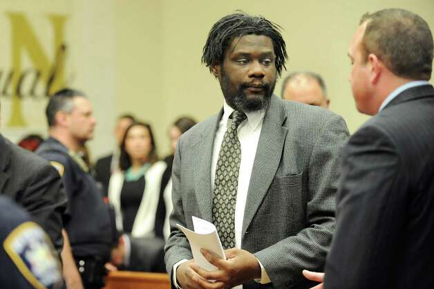 Herman Robinson, center, speaks with public defender intern Nathan Writer, right, following Robinson's guilty verdict on Friday, April 24, 2015, at Schenectady County Court in Schenectady, N.Y. Robinson will be sentenced 100 years to life for repeatedly raping a girl over a several year span and then delivering and killing the baby they conceived. (Cindy Schultz / Times Union) Photo: Cindy Schultz / 00031584A