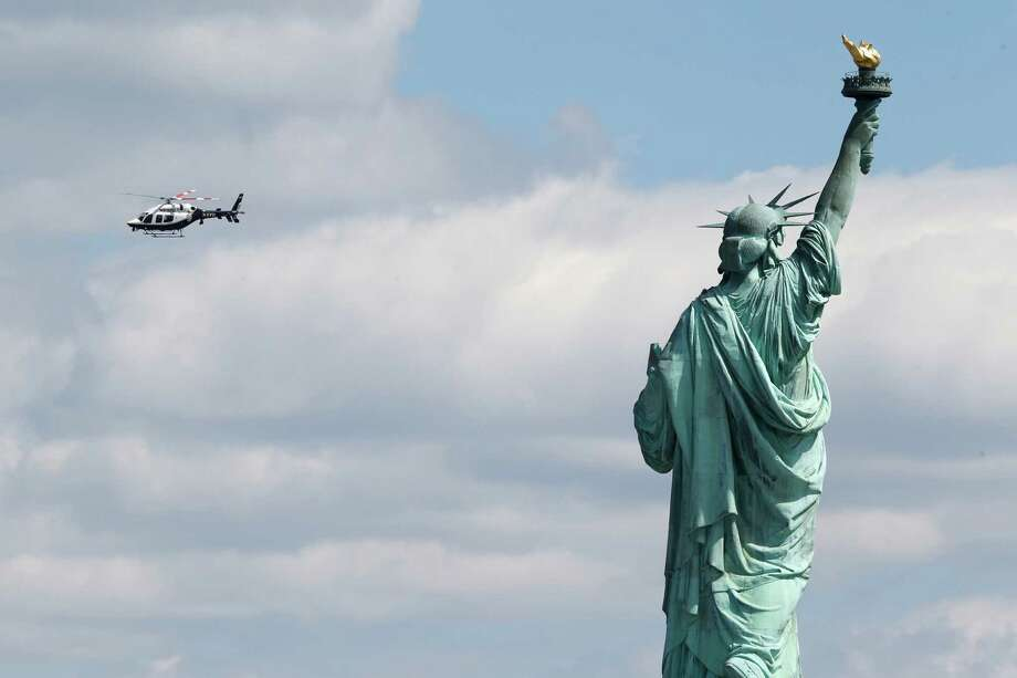 A New York Police helicopter circles over  Liberty Island where the Statue of Liberty was evacuated with officers responding to a report of a suspicious package seen from Jersey City, N.J., Friday, April 24, 2015. Visitors are posting photos online showing hundreds of people being herded toward a ferry landing. Tourists say they were taken off boats while trying to leave nearby Ellis Island. Those vessels then were used to evacuate Liberty Island. (AP Photo/Julio Cortez) ORG XMIT: NJJC108 Photo: Julio Cortez / AP