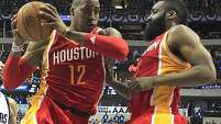 Houston Rockets center Dwight Howard  left, pulls in a rebound as Houston Rockets guard James Harden  right, looks on during of Game 3 in the first round of NBA basketball playoffs against the Dallas Mavericks at the American Airlines Center Friday, April 24, 2015, in Dallas. ( James Nielsen / Houston Chronicle )